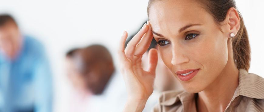 Frau im Büro mit Kopfschmerz